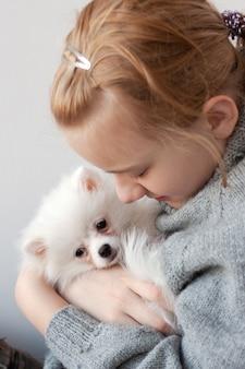Een meisje met blond haar in een grijze trui houdt een witte, pluizige pommerse puppy in haar armen, knuffelt de puppy naar haar toe, knuffelt de puppy.