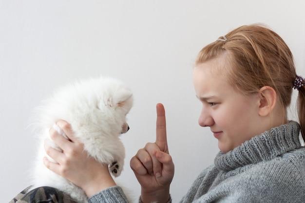 Een meisje met blond haar in een grijze trui, met een streng gezicht, houdt een witte, pluizige pommerse puppy in haar armen en schudt haar wijsvinger naar de puppy.