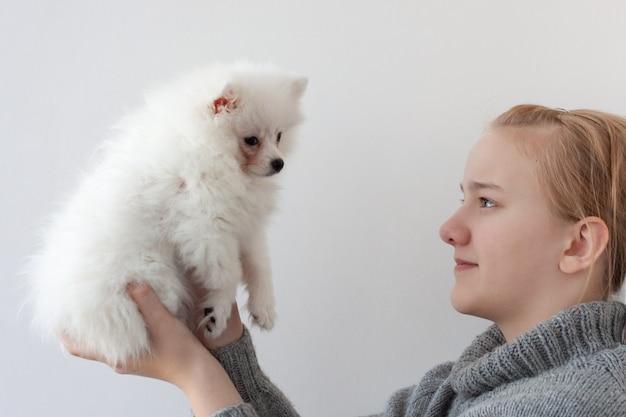 Een meisje met blond haar in een grijze trui, met een witte, pluizige pommerse puppy, hief de puppy met beide handen op en kijkt naar de puppy.