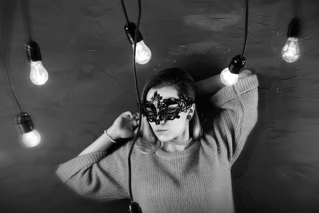 Een meisje met blond haar in een zwart masker poseert