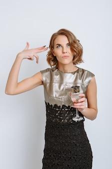 Een meisje met champagne in haar hand. het meisje maakt een gebaar alsof ze zichzelf met een pistool neerschiet.