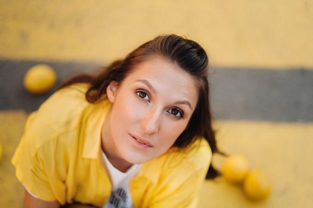 Een meisje met citroenen in een geel shirt, korte broek en zwarte schoenen zit op een gele voetgangersoversteekplaats in de stad