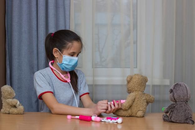 Een meisje met donker haar schoolleeftijd met medisch masker speelt in het ziekenhuis met speelgoedvaccinaties