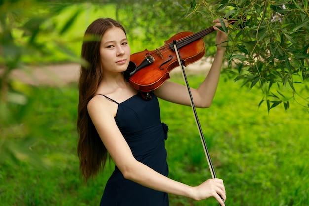 Een meisje met een aziatische uitstraling speelt viool in de natuur. hoge kwaliteit foto