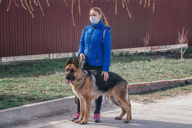 Een meisje met een beschermend medisch masker laat een hond op straat lopen. vrije tijd met een huisdier tijdens quarantaine. loop met een duitse herder