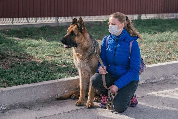 Een meisje met een beschermend medisch masker laat een hond op straat lopen. vrije tijd met een huisdier tijdens quarantaine. zelfisolatie en beschermingsmodus.