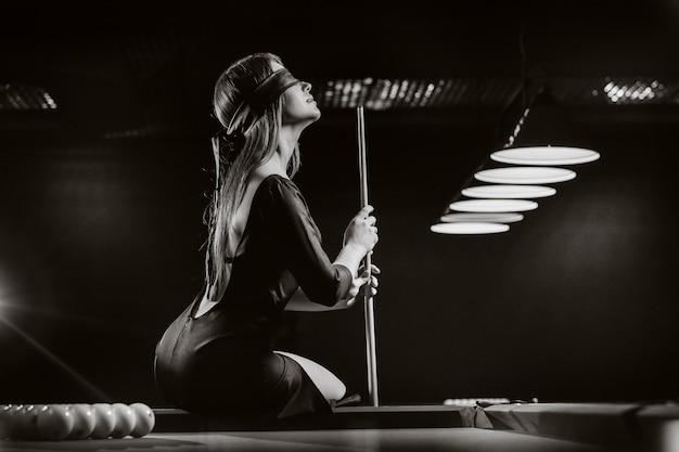 Een meisje met een blinddoek en een keu in haar handen zit op een tafel in een biljartclub. russisch biljart. zwart-wit foto.