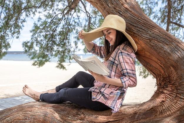Een meisje met een boek rust op een boom bij de zee. rust en ontspanning concept.