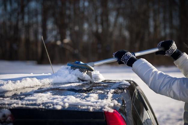 Een meisje met een borstel in haar handen reinigt het dak van de auto is bedekt met een grote laag sneeuw