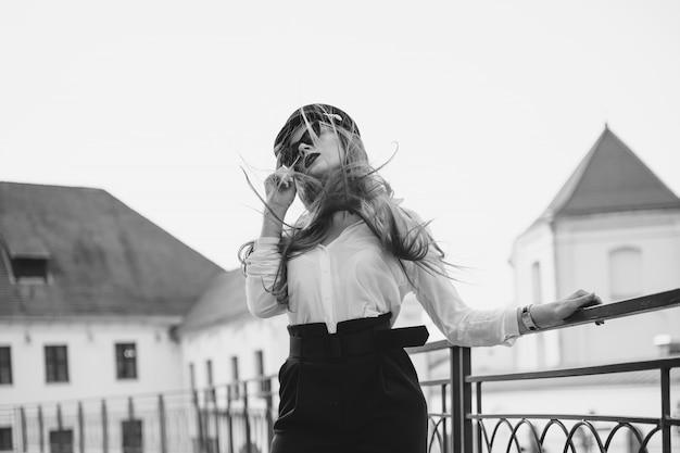 Een meisje met een bril en een hoed loopt door de stad