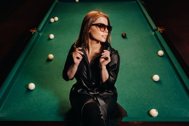 Een meisje met een bril zit op een pooltafel in een club.russisch biljart.