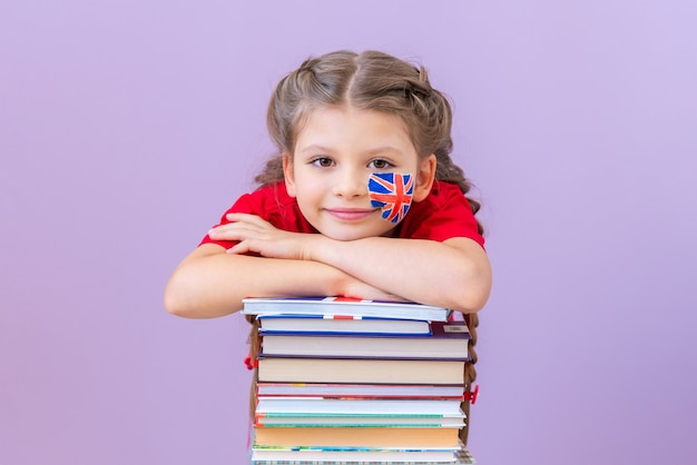 Een meisje met een britse vlag op haar wang leunde tegen een stapel boeken.