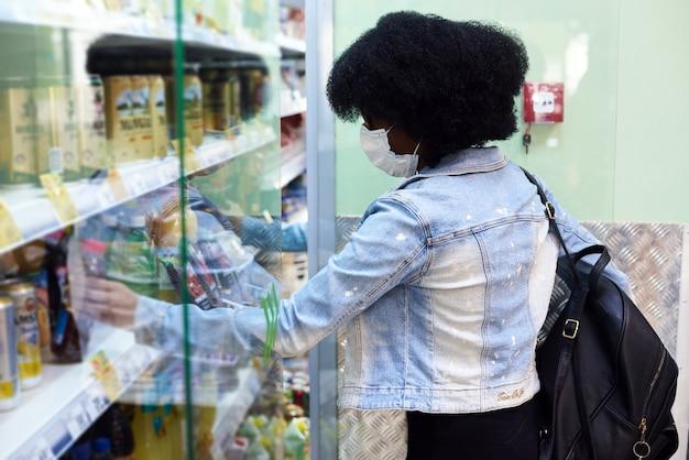 Een meisje met een donkere huidskleur kiest producten met een beschermend masker. het concept van de coronavirus pandemie en virusbescherming.