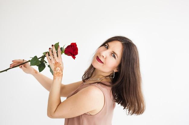 Een meisje met een europese uitstraling poseert in een licht interieur, het meisje houdt een roos vast