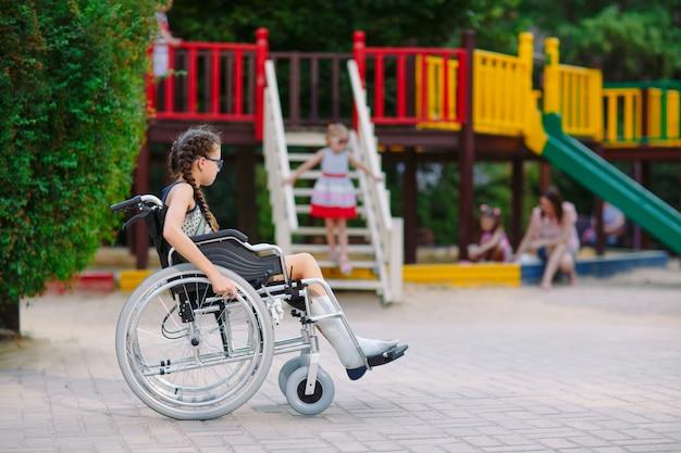 Een meisje met een gebroken been zit in een rolstoel voor de speeltuin.