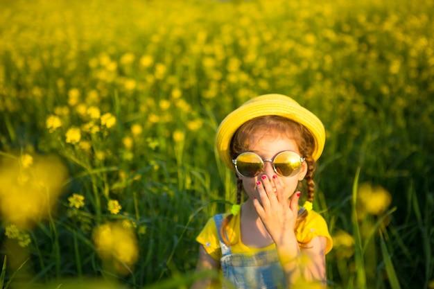 Een meisje met een gele hoed en een ronde bril kijkt naar de zon in een zomerbloeiend veld. zomertijd, zonsondergang, vakantie, zonnebrandmiddelen, allergieën, muggenspray.