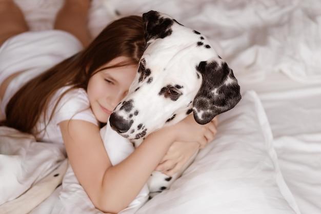 Een meisje met een gevlekte dalmatiër ligt op een wit bed. jong meisje knuffelt een witte en zwarte hond liggend op een wit vel.