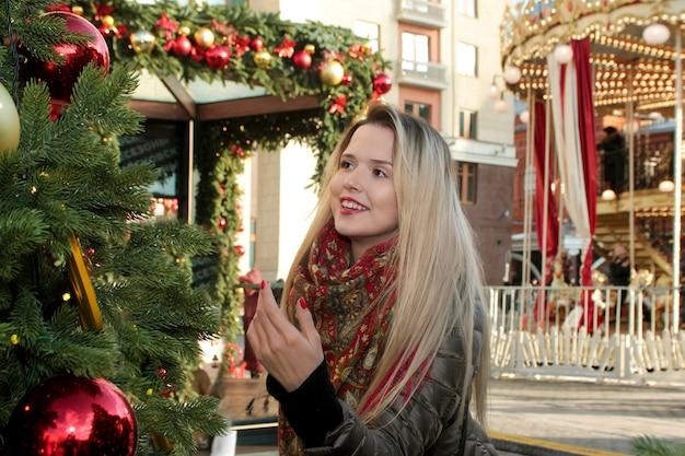 Een meisje met een glimlach op de achtergrond van een kerstboom