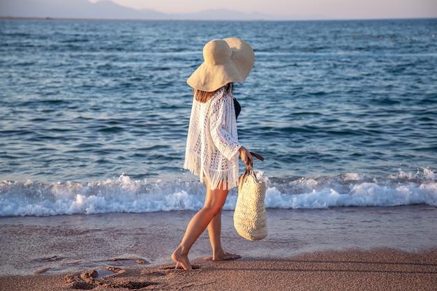 Een meisje met een grote hoed en een rieten tas loopt langs de zeekust. zomer vakantie concept.