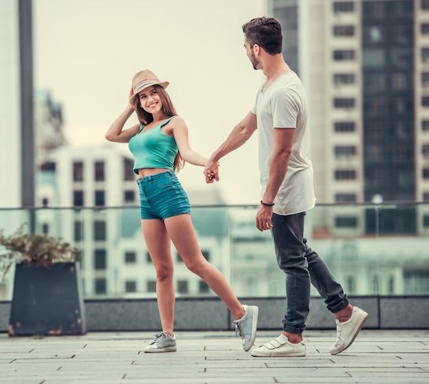 Een meisje met een hoed en een knappe man lopen.
