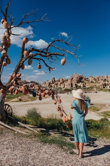 Een meisje met een hoed en een roze jurk staat bij een boom met keramische schalen in capadocia