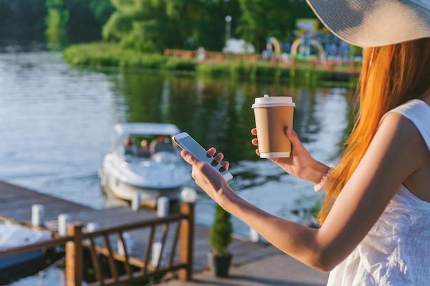 Een meisje met een hoed houdt een smartphone met koffie in haar handen. op de achtergrond waterwallen met een plezierboot.