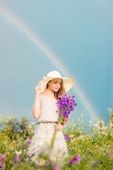 Een meisje met een hoed staat met een boeket wilde bloemen op de achtergrond van de lucht met een regenboog
