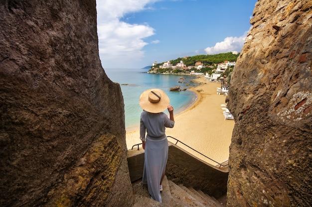 Een meisje met een hoed staat op een berghelling met uitzicht op de zee en het strand in italië.