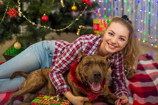 Een meisje met een hond onder een kerstboom