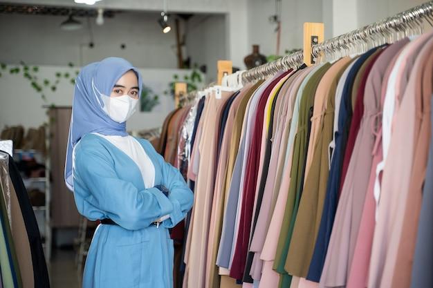 Een meisje met een hoofddoek die een blauw masker draagt en haar armen kruist, staat is