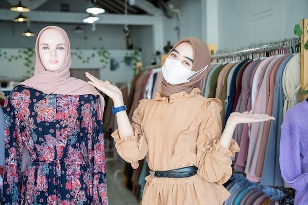 Een meisje met een hoofddoek die een masker met haar handen draagt, laat iets zien