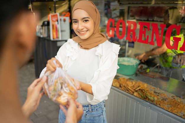 Een meisje met een hoofddoek die gefrituurd voedsel verkoopt, geeft een plastic zak gefrituurd voedsel