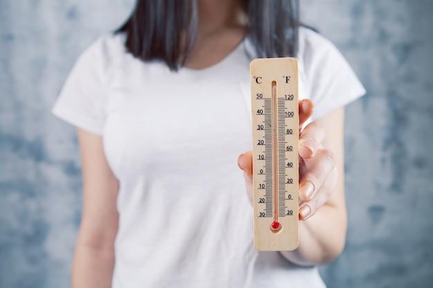 Een meisje met een huisthermometer in haar hand