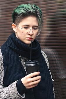 Een meisje met een jas en een sjaal drinkt in de herfst koffie op straat. afhaalmaaltijden.
