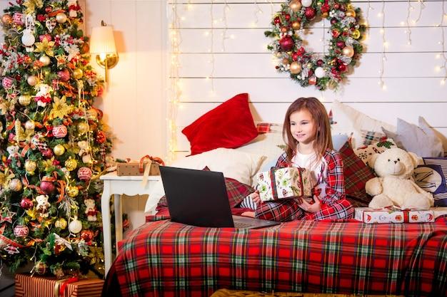 Een meisje met een kerstcadeau in haar handen zit in haar pyjama op een bed tegenover een laptop in een versierde slaapkamer.
