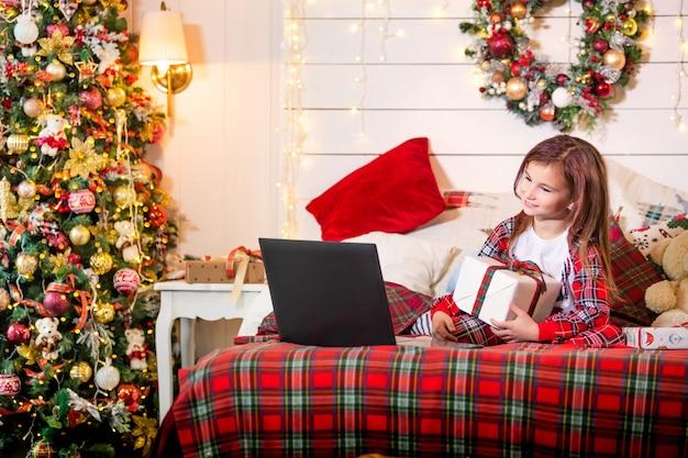 Een meisje met een kerstcadeau in haar handen zit in haar pyjama op het bed voor een laptop tegen de achtergrond van een kerstboom.