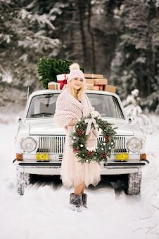 Een meisje met een kerstkrans in haar handen bedekt met een retro auto op een sneeuwbos