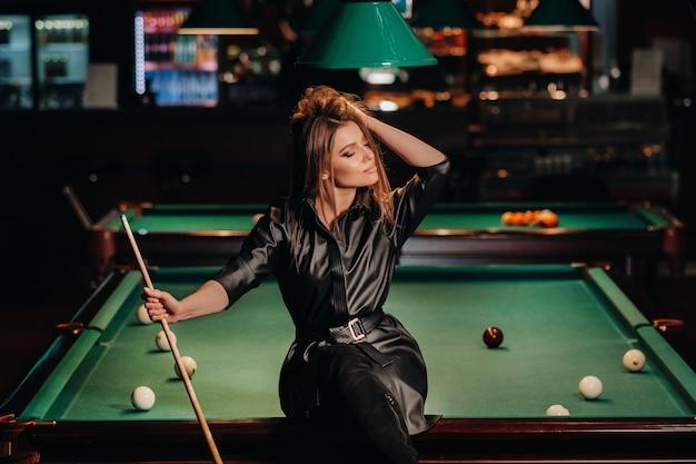 Een meisje met een keu in haar handen zit op een tafel in een biljartclub. russisch biljart.