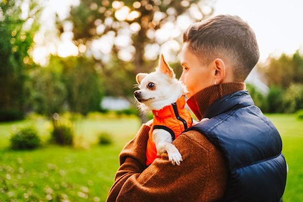 Een meisje met een kort kapsel houdt een chihuahua-hond in een oranje vest. hoge kwaliteit foto