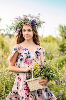 Een meisje met een krans van wilde bloemen op haar hoofd staat in een veld