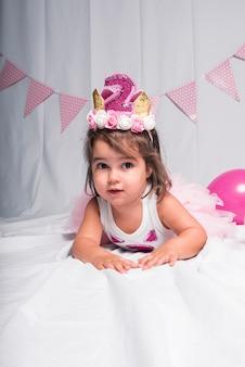 Een meisje met een kroon liggend op de vloer op wit.