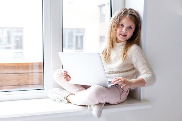 Een meisje met een laptop zit thuis op de vensterbank en kijkt