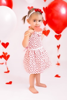 Een meisje met een lolly op de achtergrond van rode ballonnen en slingers in harten.