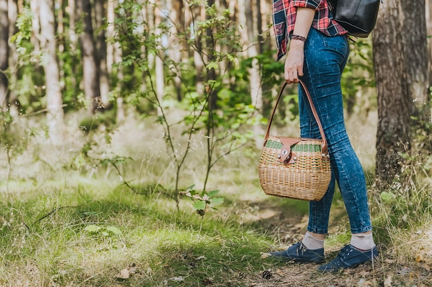 Een meisje met een mand in de hand loopt door het bos. concept rond het thema openluchtrecreatie.