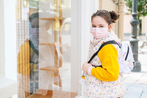 Een meisje met een masker op haar gezicht kijkt naar een etalage. het meisje draagt een gele trui en rugzak