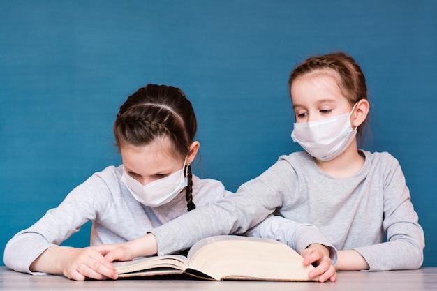 Een meisje met een medisch masker in quarantaine leest een boek en een ander meisje met een masker neemt het van haar aan. onderwijs voor geïsoleerde kinderen in een epidemie