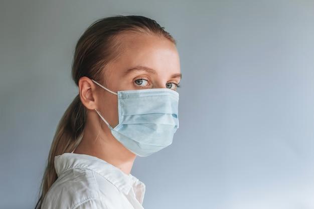 Een meisje met een medisch masker. kopieer ruimte