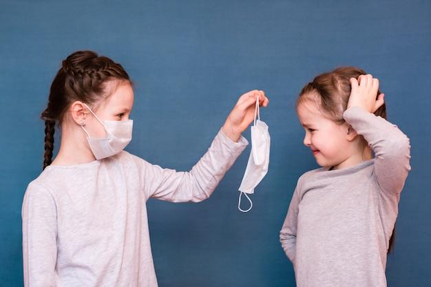 Een meisje met een medisch masker stelt voor om een schoon masker naar een ander meisje te brengen. kinderbescherming