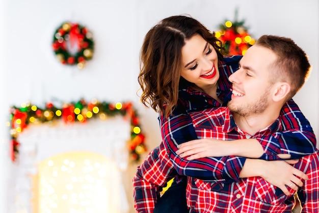 Een meisje met een mooie make-up die een man achter haar nek omhelst van achteren en hij kijkt haar aan en lacht. ze vermaken zich in de kamer met kerstversieringen