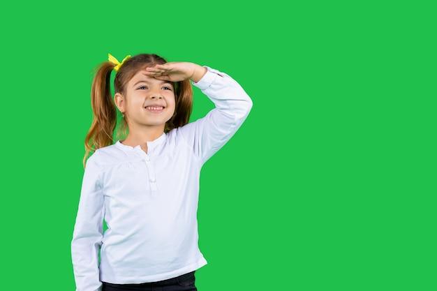 Een meisje met een oprechte glimlach en paardenstaarten kijkt in de verte en houdt haar hand tegen haar hoofd groen